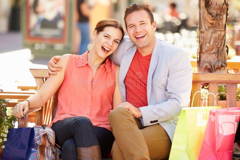 Jong Paar die met het Winkelen Zakken rusten die in Wandelgalerij zitten royalty-vrije stock foto