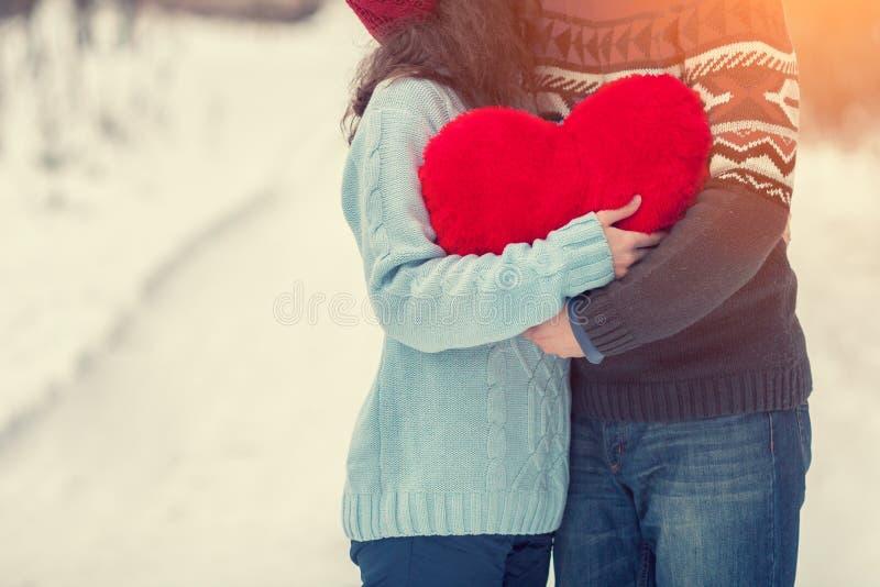 Jong paar die met rood hart in openlucht in de sneeuwwinter koesteren royalty-vrije stock afbeelding
