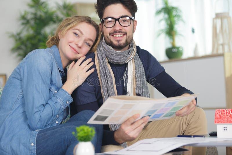 Jong paar die nieuw huisbinnenland ontwerpen royalty-vrije stock foto