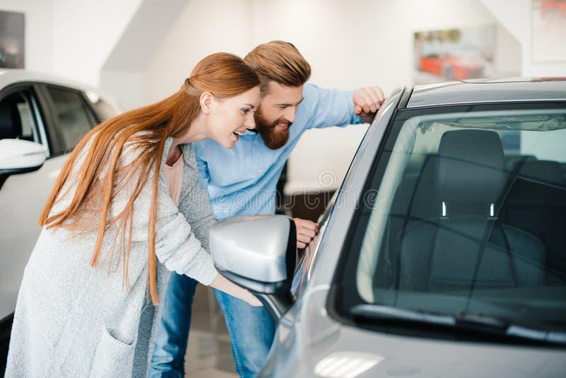 Jong paar die nieuwe auto in toonzaal bekijken royalty-vrije stock afbeelding