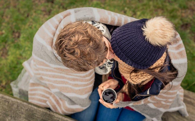 Jong paar die onder deken met hete drank in openlucht kussen royalty-vrije stock afbeeldingen