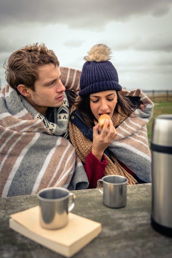 Jong paar die onder deken muffin in openlucht in een koude dag eten stock fotografie