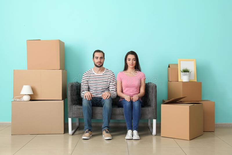 Jong paar die op bank dichtbij dozen binnen rusten Het bewegen zich in Nieuw Huis royalty-vrije stock foto