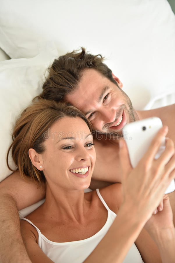 Jong paar die op bed liggen die smartphone gebruiken royalty-vrije stock foto's