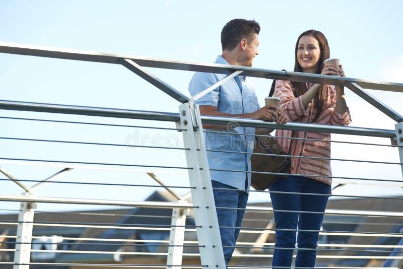 Jong Paar die op Brug in het Stedelijke Plaatsen Holding spreken Meeneem stock foto's