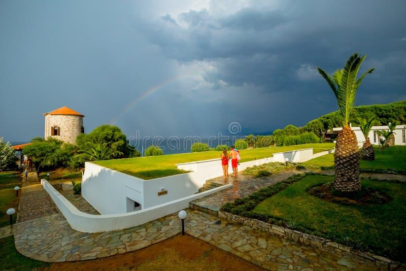 Jong Paar die op de Onweershemel met een Mooie Regenboog letten over het Overzees in een Grieks Hotel royalty-vrije stock foto's