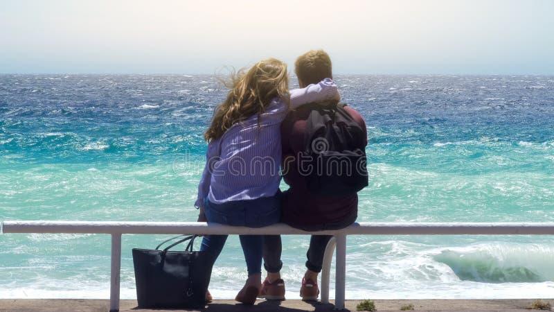 Jong paar die op de pijp van het wachtspoor op winderige zonnige dag koesteren, die stormachtige oceaan onder ogen zien stock fotografie