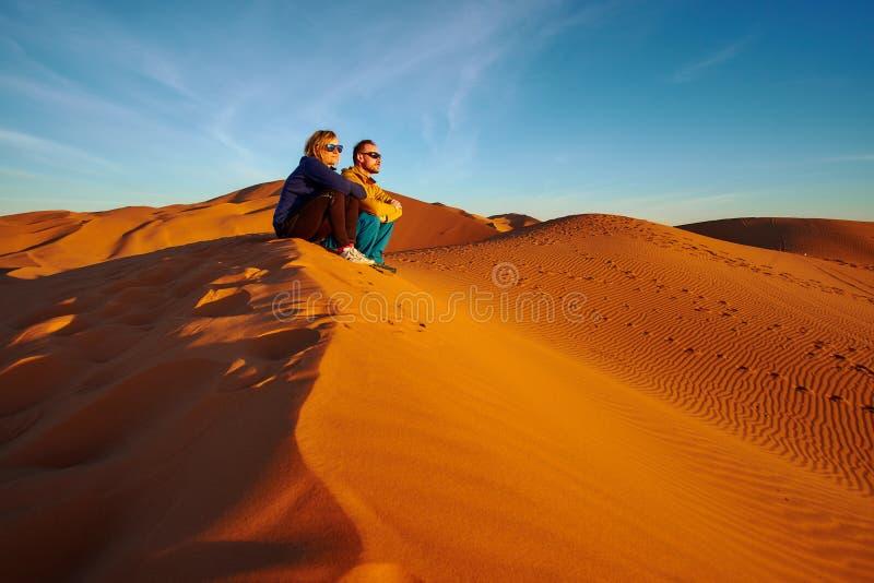 Jong paar die op de zonsopgang op het zandduin letten in de woestijn van de Sahara stock foto