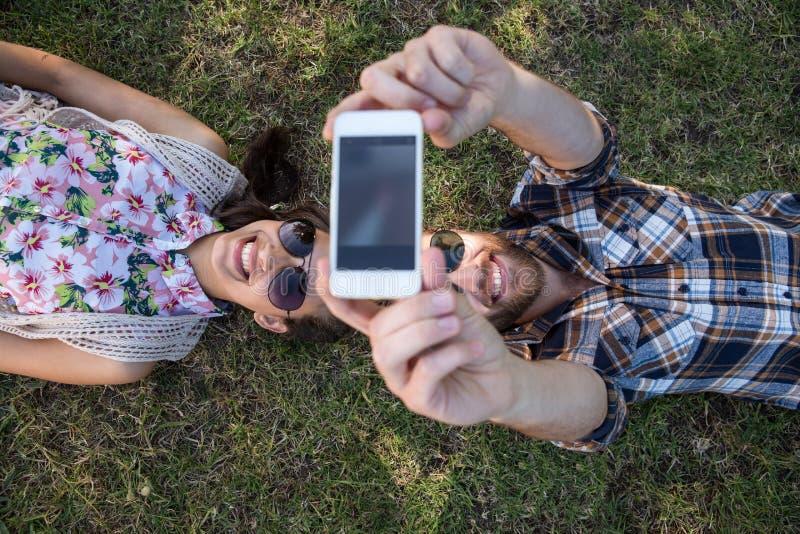 Jong paar die op gras liggen die selfie nemen stock foto