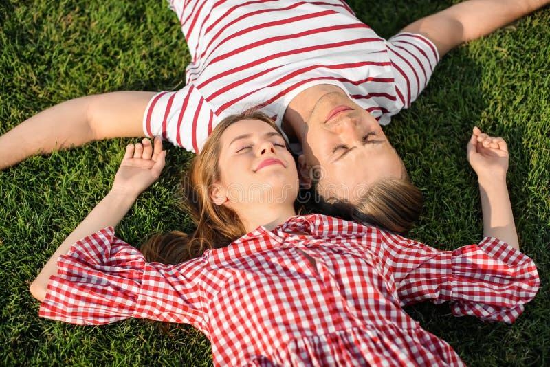 Jong paar die op groen gras in openlucht liggen stock foto