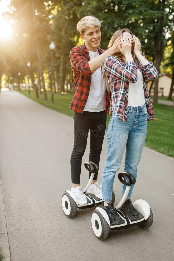 Jong paar die op gyroscoopraad lopen in de zomerpark royalty-vrije stock afbeeldingen