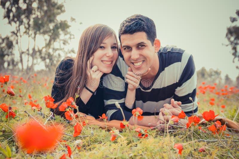 Jong paar die op het gras in een gebied van rode papavers liggen en sm royalty-vrije stock foto's