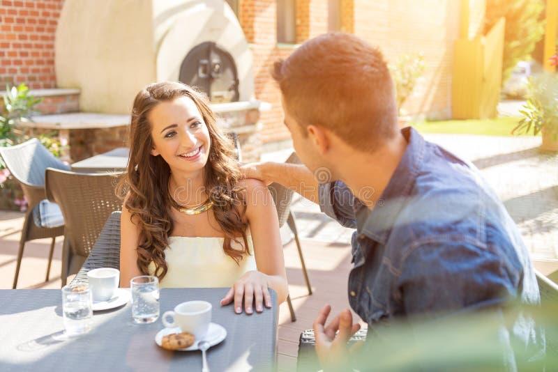 Jong paar die op het terras van het restaurant spreken, terwijl het eten stock foto's