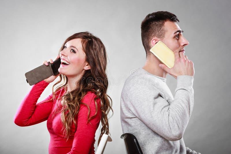 Jong paar die op mobiele telefoons spreken stock foto's