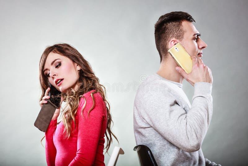 Jong paar die op mobiele telefoons spreken stock fotografie
