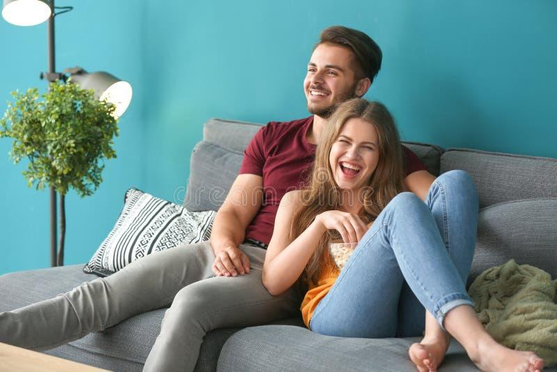 Jong paar die op TV op bank thuis letten stock foto