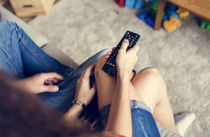 Jong paar die op TV samen thuis letten royalty-vrije stock fotografie