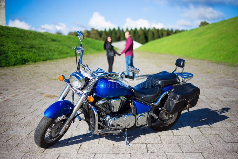 Jong paar die op weg en retro motorfiets lopen stock foto