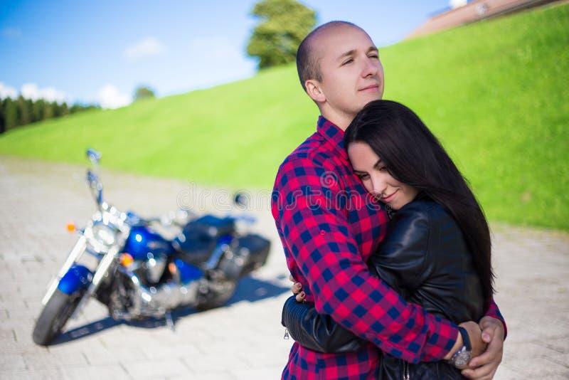 Jong paar die op weg met retro motorfiets koesteren royalty-vrije stock foto's