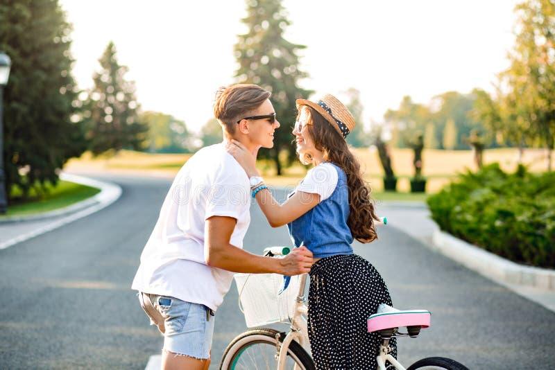 Jong paar die op weg op zonsondergang koesteren Het mooie meisje met lang krullend haar in hoed en lange rok houdt een knappe fie stock fotografie