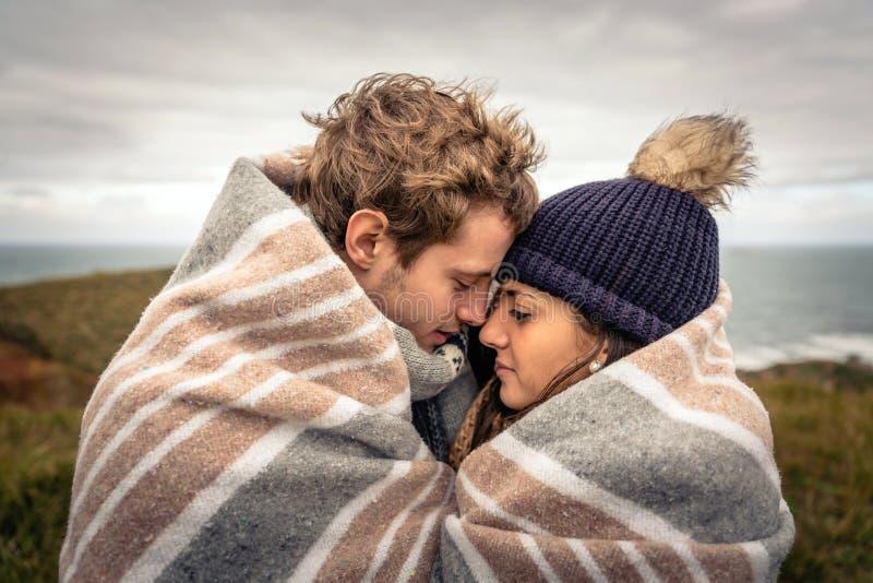 Jong paar die in openlucht onder deken in een koude dag omhelzen stock foto