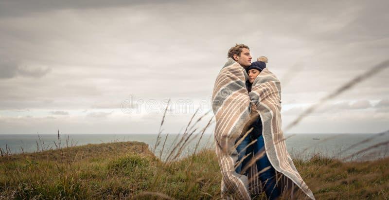 Jong paar die in openlucht onder deken in een koude dag omhelzen stock afbeeldingen