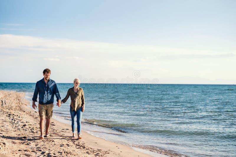 Jong paar die in openlucht op strand lopen, die handen houden De ruimte van het exemplaar stock afbeeldingen