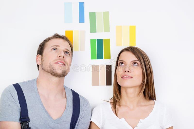 Jong paar die over nieuw decor proberen te beslissen royalty-vrije stock afbeelding