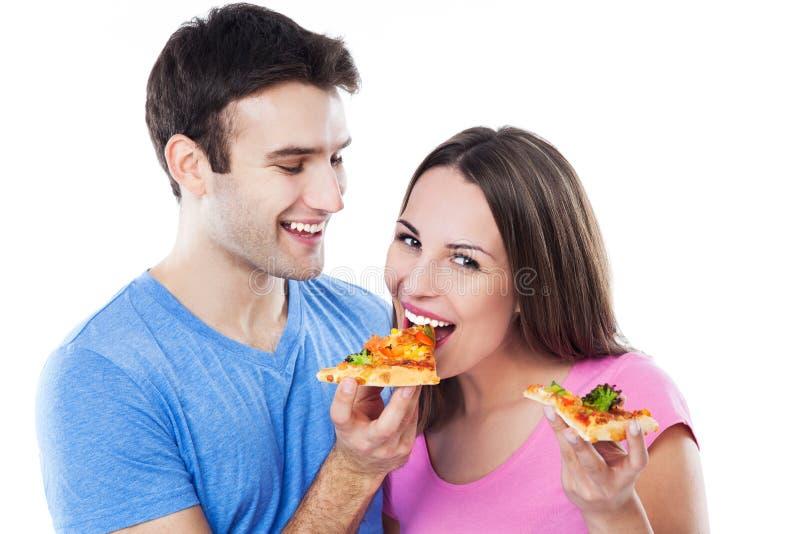 Jong paar die pizza eten stock afbeeldingen