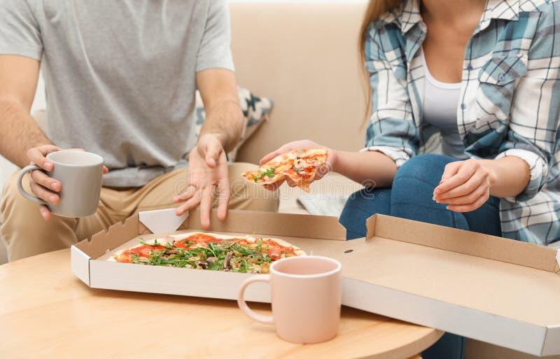 Jong paar die pizza voor lunch hebben thuis, close-up stock foto