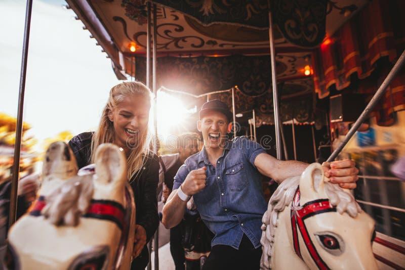 Jong paar die pret op carrousel hebben royalty-vrije stock fotografie