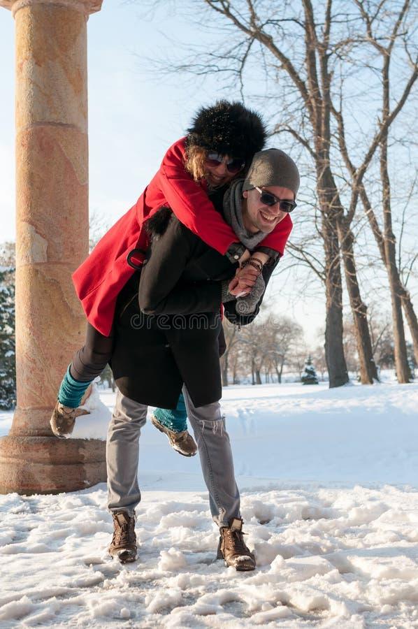 Jong paar die pret op de sneeuw hebben royalty-vrije stock foto's