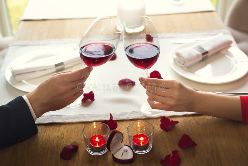 Jong paar die romantisch diner in het restaurant het drinken close-up van wijntoejuichingen hebben stock foto's