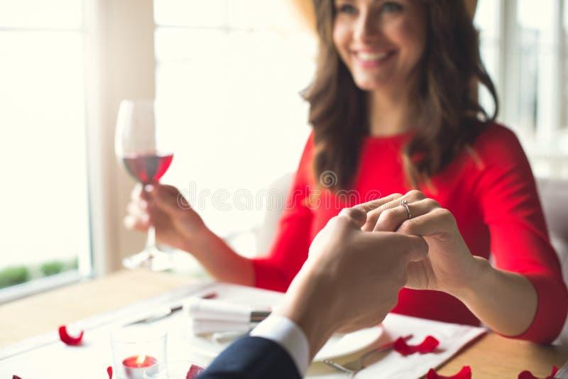 Jong paar die romantisch diner in het restaurant hebben die voorstelring het glimlachen dragen royalty-vrije stock foto's
