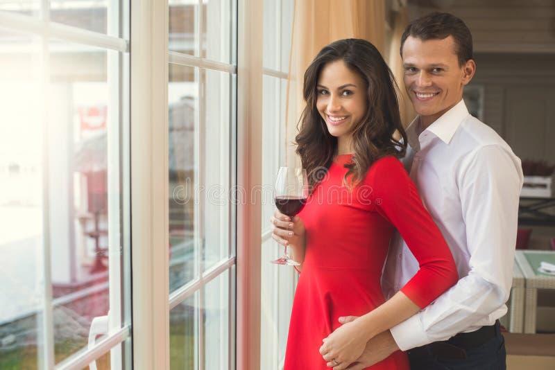 Jong paar die romantisch diner in het restaurant hebben die zich dichtbij het venster bevinden royalty-vrije stock afbeelding