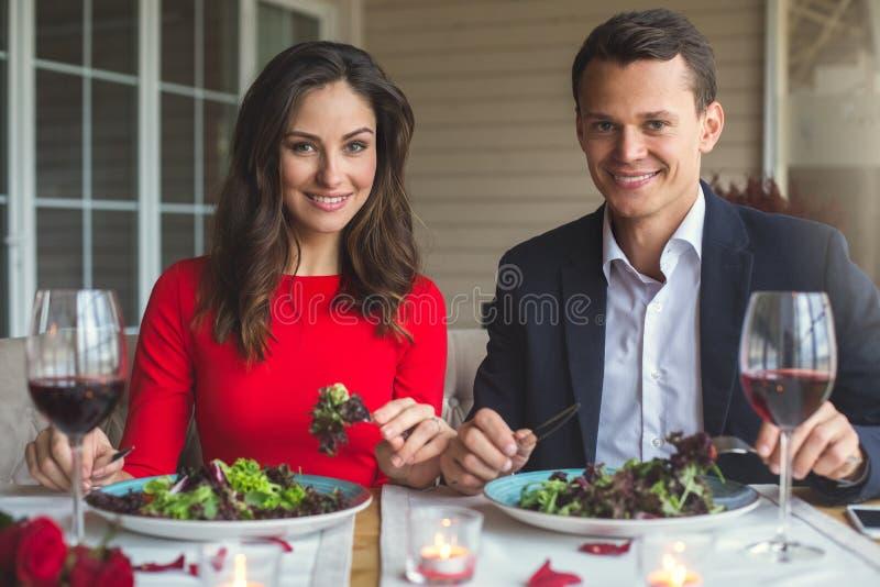Jong paar die romantisch diner in restaurant eten hebben die camera kijken royalty-vrije stock foto