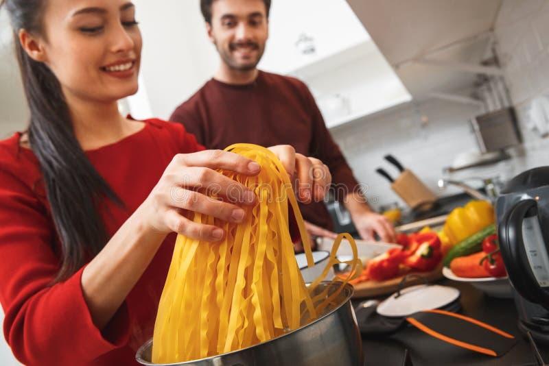 Jong paar die romantische avond thuis in het keuken het koken maaltijd samen close-up hebben stock fotografie