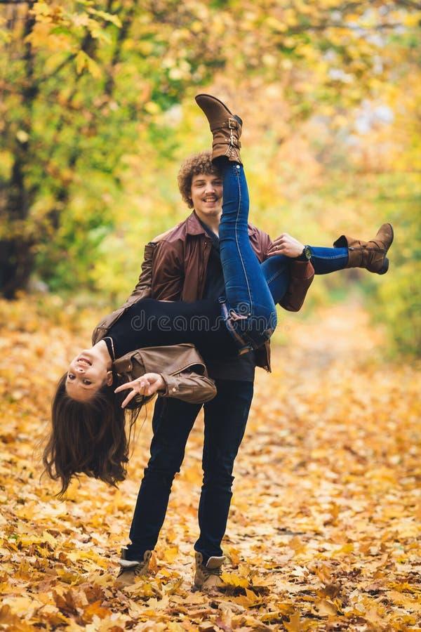 Jong paar die rond in de herfstpark voor de gek houden royalty-vrije stock foto