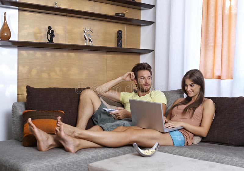 Jong paar die rust in woonkamer hebben royalty-vrije stock afbeeldingen