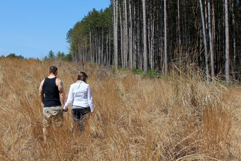 Jong paar die samen in open grasrijke weide lopen stock fotografie