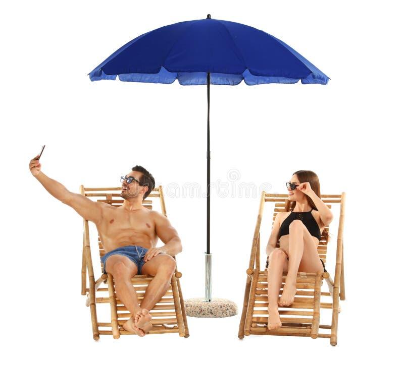 Jong paar die selfie op lanterfanters onder paraplu tegen witte achtergrond nemen De toebehoren van het strand stock foto's