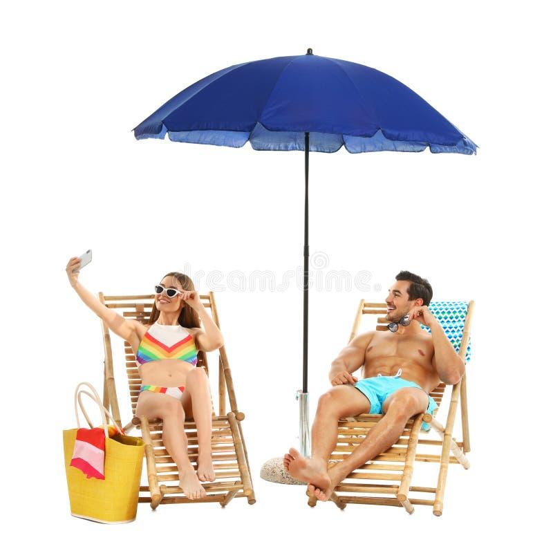 Jong paar die selfie op zonlanterfanters onder paraplu tegen witte achtergrond nemen Strand royalty-vrije stock foto's