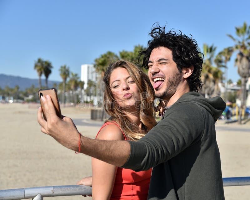 Jong paar die selfies op vakantie nemen stock foto