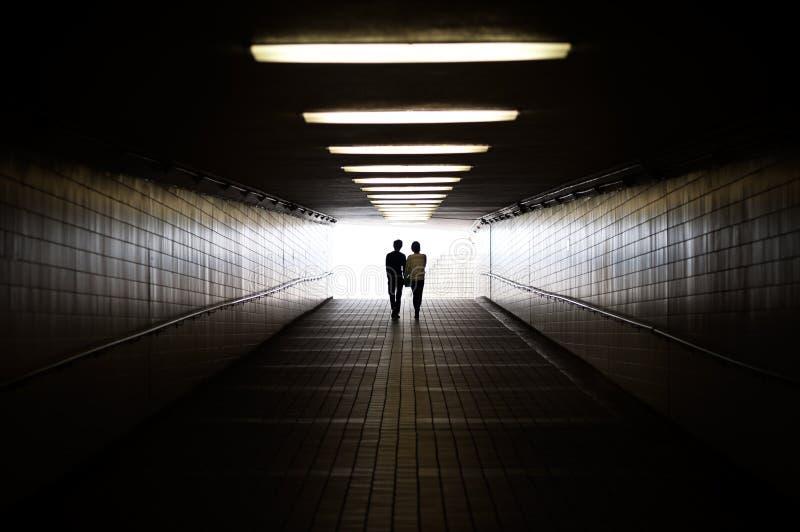 Jong paar die in silhouet naar uitgang van voetonderdoorgang lopen royalty-vrije stock fotografie