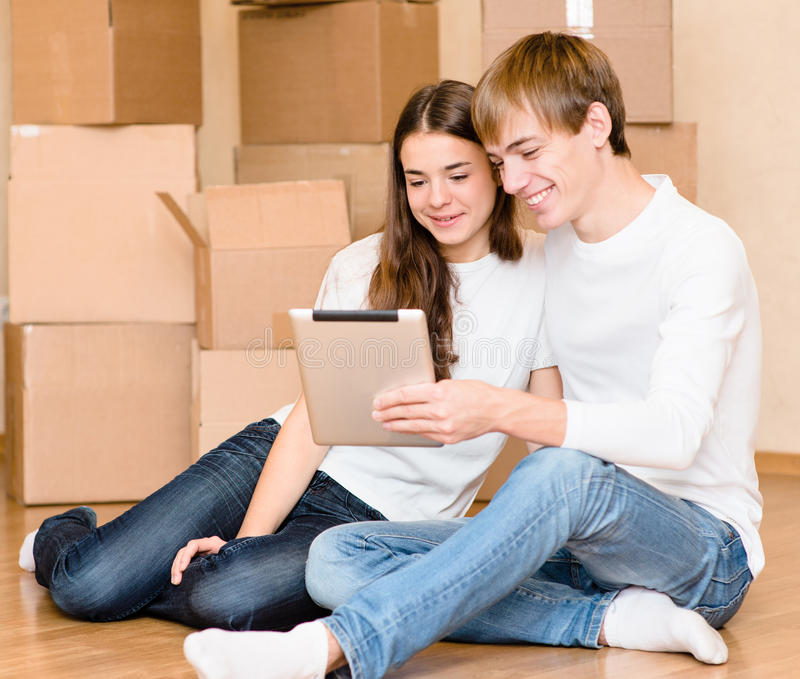 Jong paar die tabletcomputer in hun nieuw huis met behulp van royalty-vrije stock foto