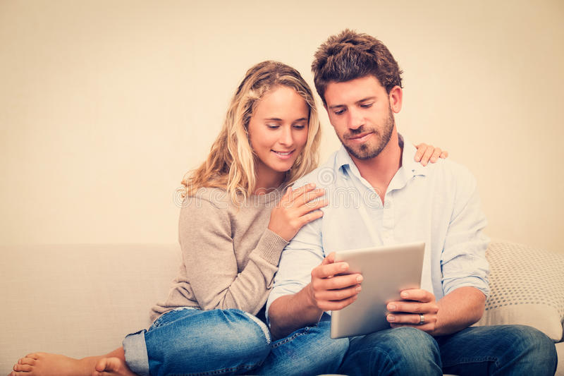 Jong paar die tabletcomputer met behulp van stock foto's