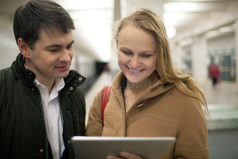 Jong paar die tabletcomputer ondergronds met behulp van in stock foto's