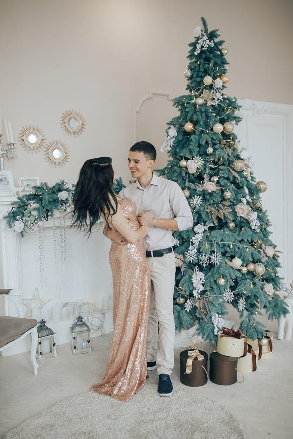Jong paar die terwijl het vieren thuis dichtbij een Kerstboom glimlachen royalty-vrije stock fotografie
