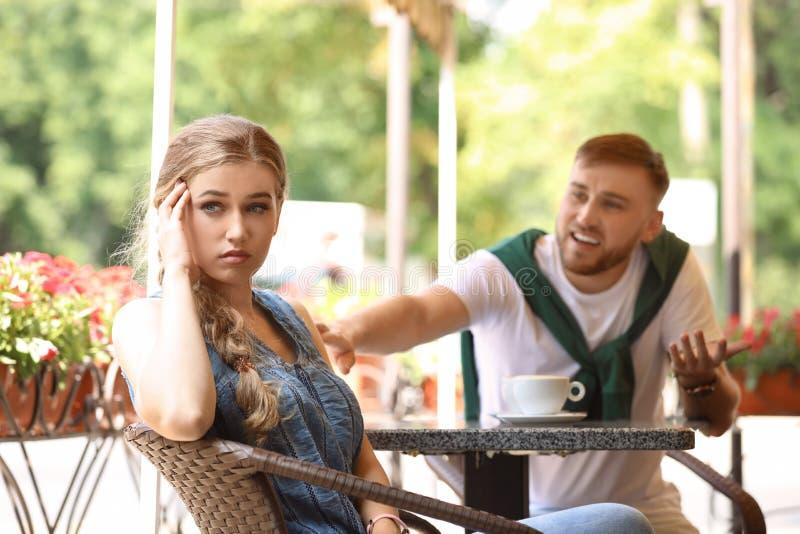 Jong paar die terwijl het zitten in koffie, in openlucht debatteren stock afbeeldingen