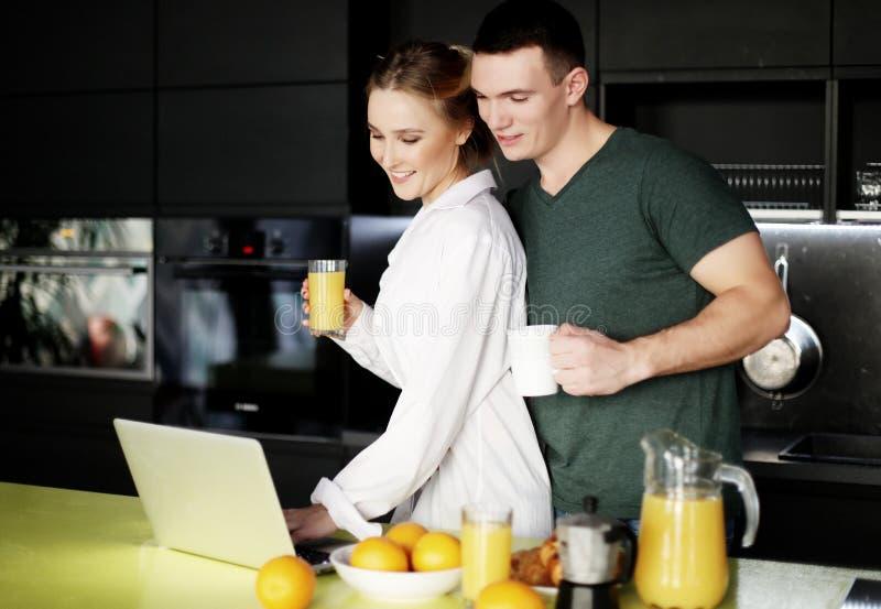 Jong paar die thuis koffie in keuken hebben en aan laptop computer werken stock afbeeldingen